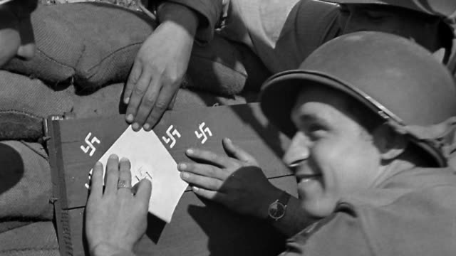 1940s close up Soldiers stencilling swastikas as symbols of number of enemies hit