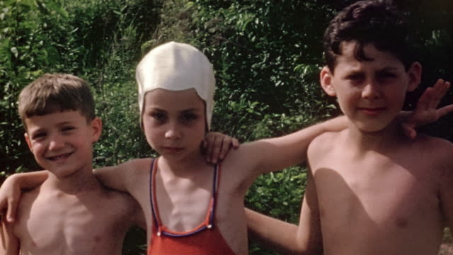 1940s close up two boys and girl wearing swimsuits posing with arms around each other / smiling at camera / Camp Eton, Rhinebeck, NY