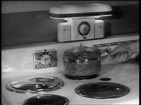 b/w 1940s close up woman's hand lifting pot from stove in kitchen - yorkville illinois stock videos & royalty-free footage