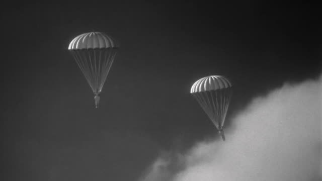 1940s composite wide shot 2 toy parachutes falling / clouds in background - fallschirmjäger stock-videos und b-roll-filmmaterial