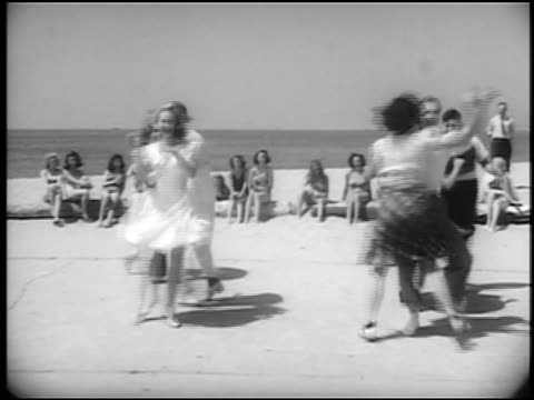 B/W 1940s couples jitterbugging on beach / female spectators in swimsuits in background / newsreel