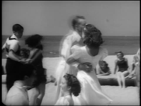b/w 1940s pan couples jitterbugging on beach / female spectators in swimsuits in background / newsreel - teenage couple stock videos & royalty-free footage