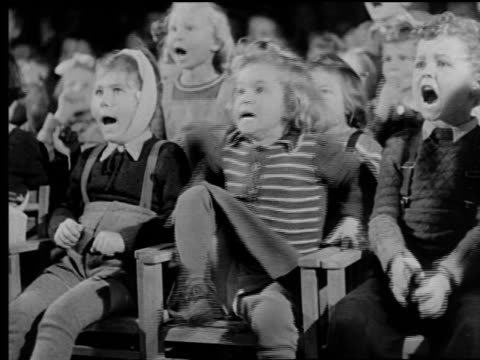 B/W 1940s crowd of children sitting in theater reacting in fear to action off camera