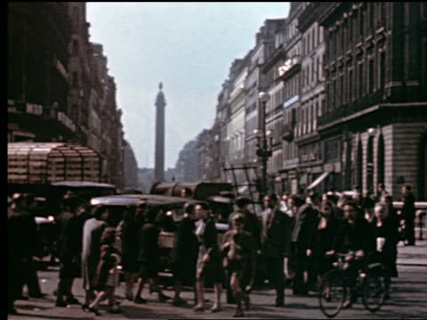 stockvideo's en b-roll-footage met 1940s crowd of people crossing street / traffic passing in foreground + colonne vendome in background / paris - colonne vendome