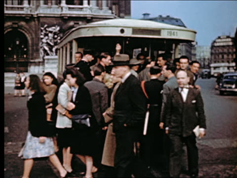 1940s crowd of people walking away from bus pulling away on place de l'opera  / paris, france - avenue de l'opera stock videos & royalty-free footage
