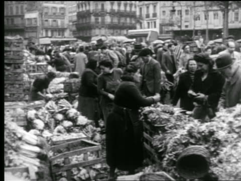 B/W 1940s crowded outdoor market / woman giving change at produce stand / Paris, France