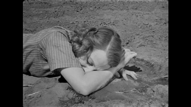 1940s distraught woman breaks down, falls to the ground, and weeps into the soil - hysteria stock videos & royalty-free footage