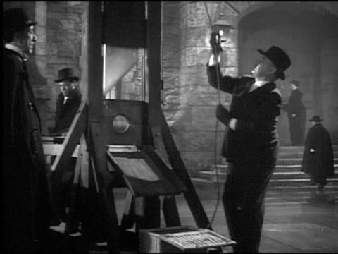 "b/w 1940s dolly shot man raising guillotine in to close up guillotine blade dropping / ""uncertain glory"" - guillotine stock-videos und b-roll-filmmaterial"