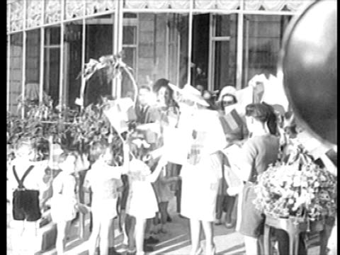 b/w 1940s eva peron in hat being greeted by children waving flags / newsreel - bandiera dell'argentina video stock e b–roll