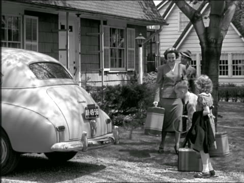 b/w 1940s family loading up trunk of car with luggage + sports equipment outside of house - 1940 stock videos and b-roll footage