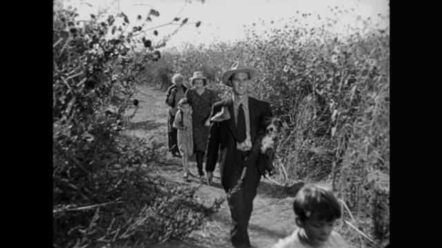vidéos et rushes de 1940s farm family walk along sunny path through the field - péquenaud