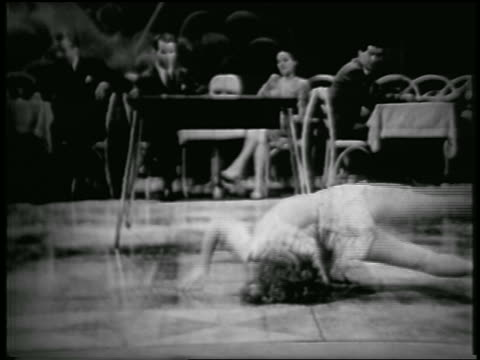 vidéos et rushes de b/w 1940s female contortionist (jacqueline hurley) performing on nightclub floor / audience at tables in background - breakdance