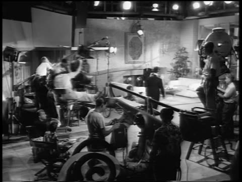 B/W 1940s film crew moving camera + cameraman on crane to follow actors on movie set in studio