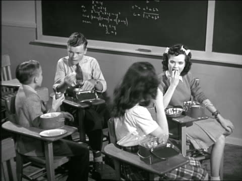 B/W 1940s four students eating lunch at desks + talking in classroom