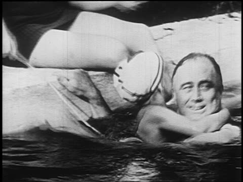 1940s franklin d. roosevelt holding child in bathing cap in swimming pool/warm spring - cuffia da nuoto video stock e b–roll