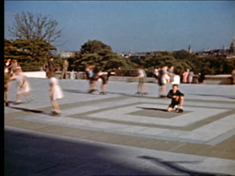 1940s PAN from children roller-skating in circle in Place du Trocadero to Eiffel Tower in background / Paris
