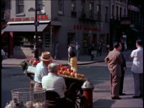 1940s fruit sellers + people walking on sidewalks + street in Chinatown / San Francisco