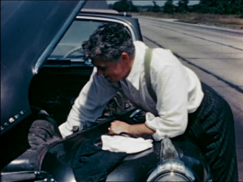 1940s frustrated man working on engine of car broken down beside highway / travelogue - anger stock videos & royalty-free footage