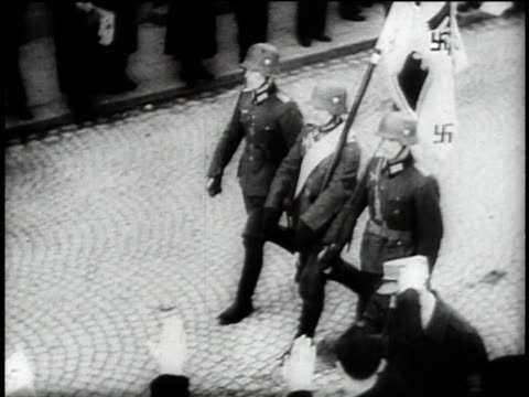 1940s TS German soldiers marching with a Nazi flag / Austria