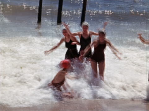 1940s group of women/teen girls in swimsuits and bathing caps playing in waves on beach / home movie