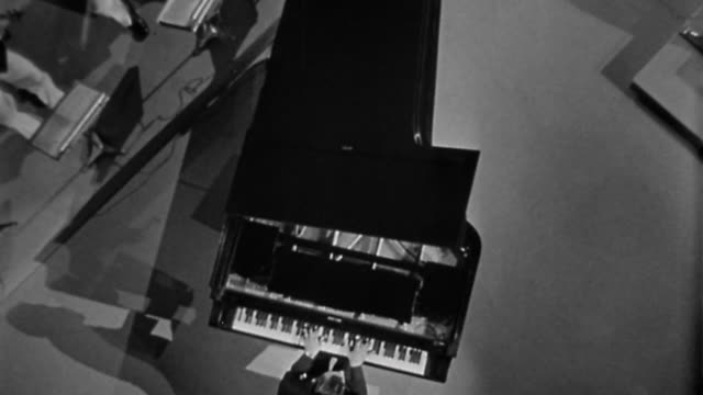 vídeos de stock e filmes b-roll de 1940s high angle close up hands on piano keyboard / zoom out to musicians, entire concert hall, heavens and clouds - pianista