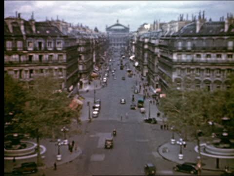 vídeos de stock, filmes e b-roll de 1940s high angle long shot l'opera garnier at far end of avenue de l'opera with traffic + people / paris, france - teatro de ópera