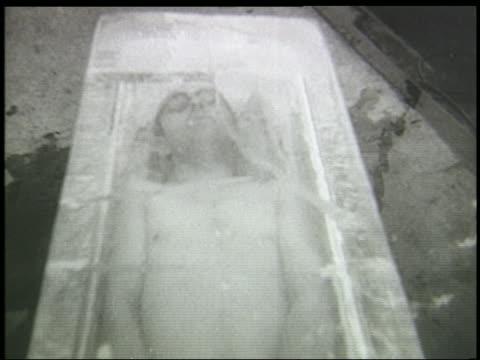 vídeos de stock, filmes e b-roll de b/w 1940s high angle man wearing glasses + swimsuit lying inside box made of ice - reclining