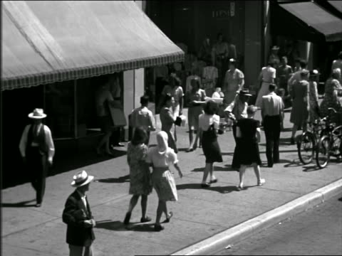 B/W 1940s high angle shoppers + pedestrians walking on city sidewalk past stores