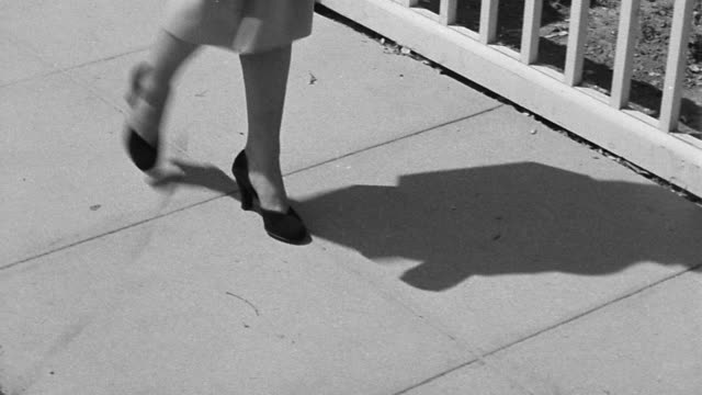 b/w 1940s high angle ms tracking shot woman's legs in skirt + high heels walking on sidewalk - human foot stock videos & royalty-free footage
