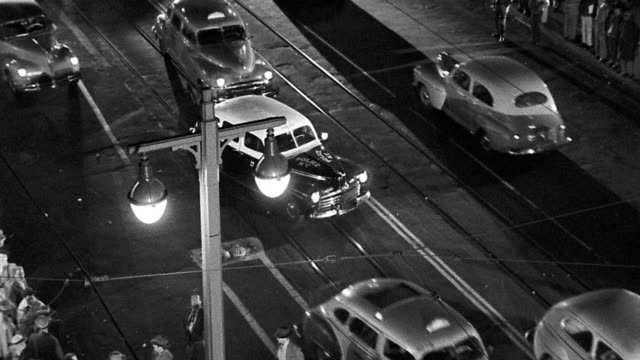 B/W 1940s high angle traffic on city street with people standing on sides at night / Los Angeles