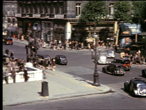 1940s high angle PAN traffic, people walking + Metro entrance in Place de l'Opera / Paris, France