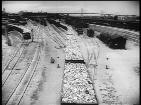 b/w 1940s high angle train loaded with scrap metal taking off from train yard / large bridge in background / newsreel - newsreel stock videos and b-roll footage