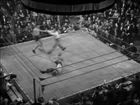 1940s high angle wide shot boxing match / boxer punching opponent / referee counting / declaring winner - 30 39 years stock videos & royalty-free footage