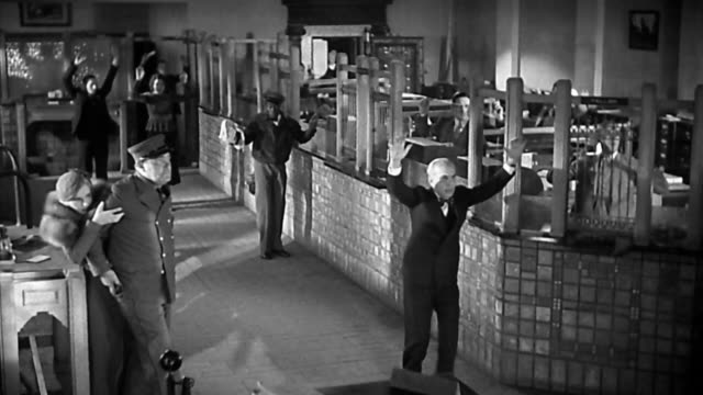 stockvideo's en b-roll-footage met 1940s high angle wide shot customers, security guard, and janitor in bank / everyone puts up hands / robbers walk in - steel