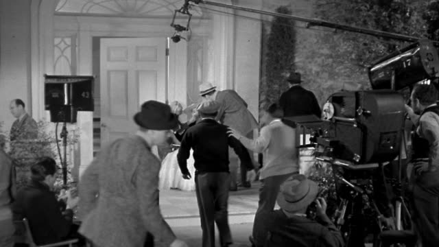 1940s high angle wide shot director, actress, and crew preparing to shoot on film set - filming stock videos & royalty-free footage