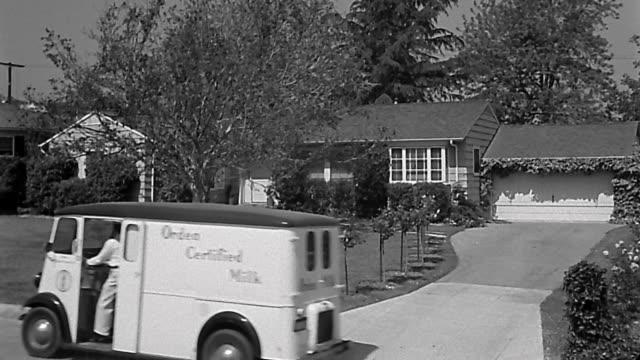 1940s high angle wide shot milk truck at suburban house / paper boy delivering newspaper / milkman in driveway - 1940~1949年点の映像素材/bロール