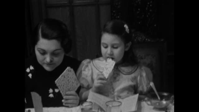 vidéos et rushes de 1940s home movie - family at dinner table eating matzo bread - judaism
