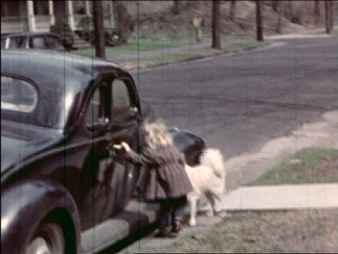 vidéos et rushes de 1940s home movie little girl with dog on leash on sidewalk trying to open car door - seulement des petites filles