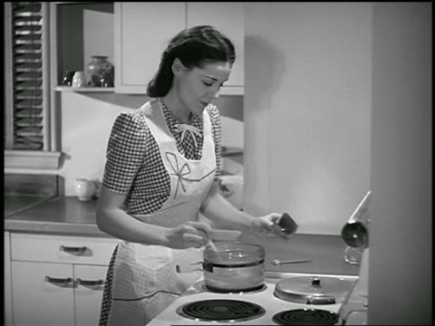 b/w 1940s housewife standing at stove cooking - 1940 stock videos & royalty-free footage