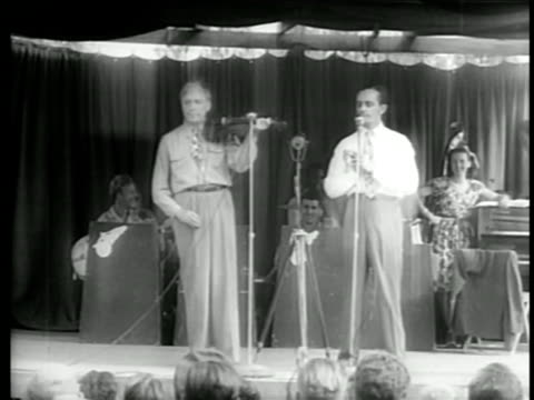 B/W 1940s Jack Benny playing violin onstage next to Larry Adler playing harmonica in USO tour / documentary