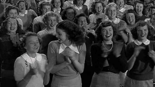 vídeos de stock, filmes e b-roll de 1940s ms large group of teenage girls (bobby soxers) standing and clapping in audience - preto e branco