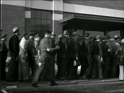 b/w 1940s pan line of male blue collar workers entering factory - 1940 bildbanksvideor och videomaterial från bakom kulisserna