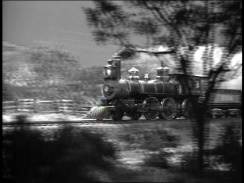 stockvideo's en b-roll-footage met 1940s ts locomotive train with multiple cars traveling through wooded area and entering dark tunnel / united states - locomotief
