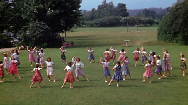 1940s long shot group of teenage girls performing folk dance on lawn