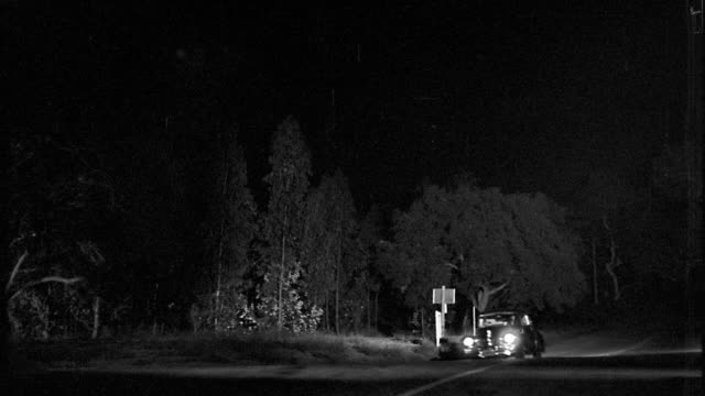 vidéos et rushes de b/w 1940s low angle pan car driving towards camera + spinning on country road at night - accident de transport