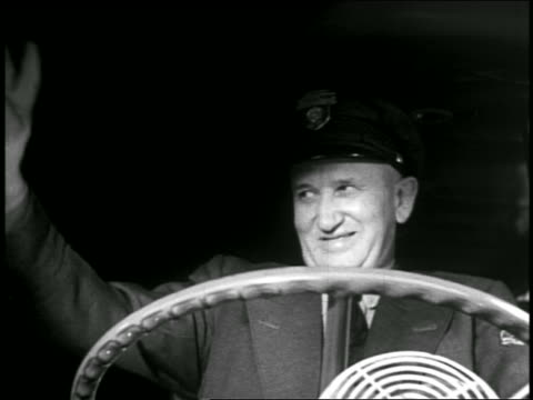 b/w 1940s low angle close up middle-aged bus driver at wheel waving + smiling - bus driver stock videos & royalty-free footage