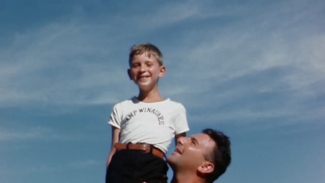 1940s low angle medium shot shirtless man holding boy on shoulders - handkamera bildbanksvideor och videomaterial från bakom kulisserna