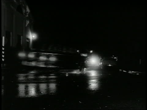 vidéos et rushes de 1940s low angle wide shot pan 2 police cars chasing car around corner at night - poursuivre