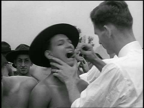 B/W 1940s male doctor examining throat of shirtless boy in Boy Scout hat / crowd of boys in background
