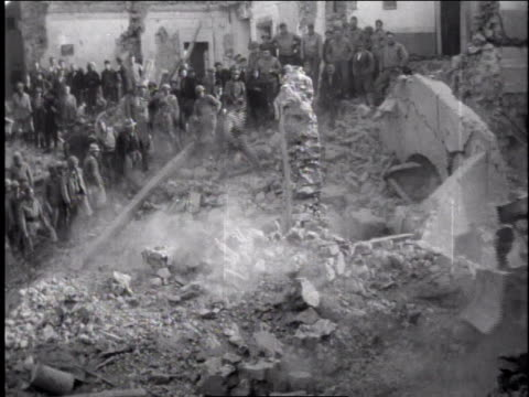 1940s man clearing rubble with bulldozer with several standing and watching, men pushing a wall over with shovels / europe - rubble stock-videos und b-roll-filmmaterial
